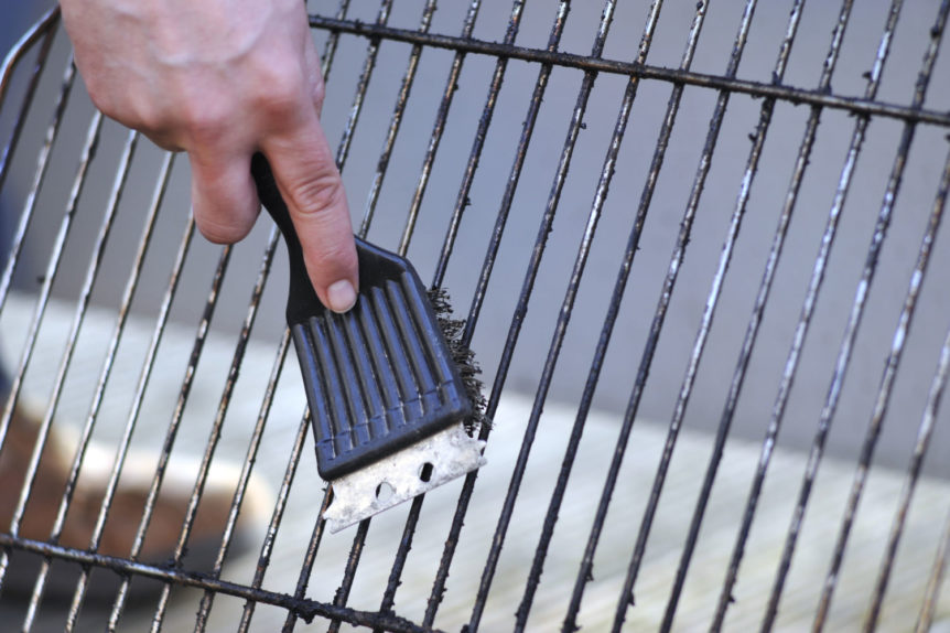 a person cleaning the grill with scrubber